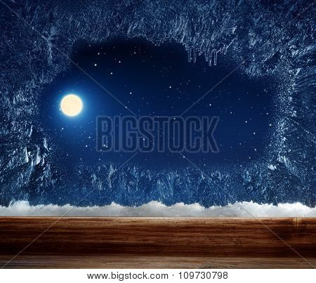 Winter window with frosted inside. Outside stars and the moon.