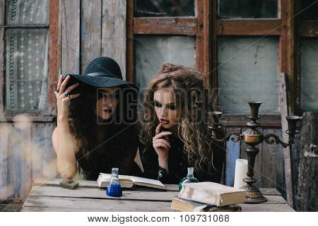 Two vintage witches perform magic ritual