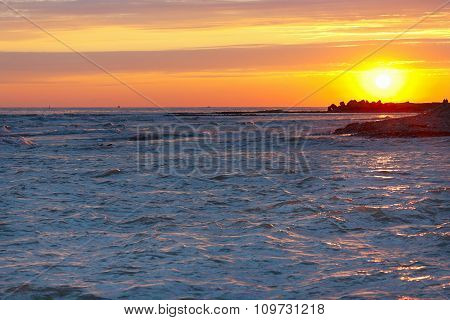 Tranquil sea sunset on stony seashore