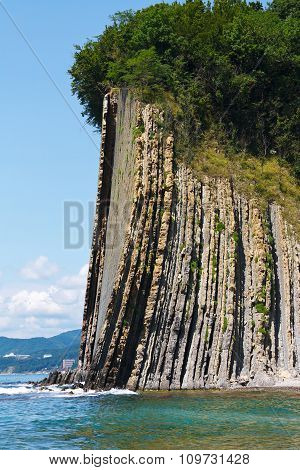 Amazing high rock with a forest at the top by sea. Rock Kiselev