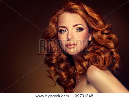 Beautiful model  girl  with long  red curled hair .