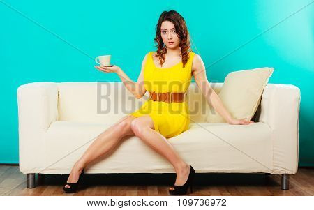Woman Sitting On Couch Holds Coffee Cup