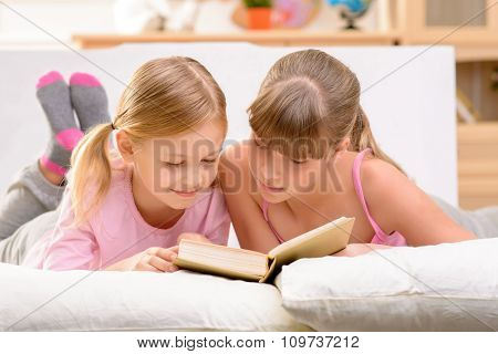 Cheerful sisters reading book
