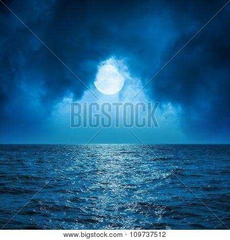full moon in clouds over dark blue sea