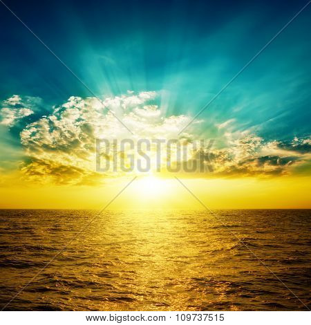 orange sunset in dark blue sky over yellow sea