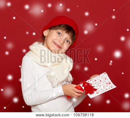happy girl in santa hat with box gift show fir tree toy on red background