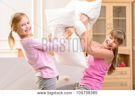 Nice little sisters fighting with pillows