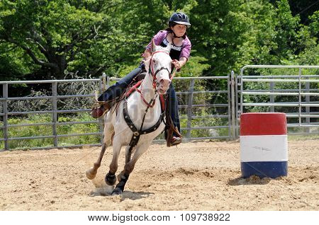 Teenage girl galloping around a turn in a barrel race