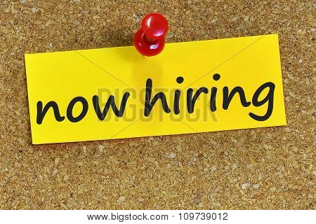 Now Hiring Word On Yellow Notepaper With Cork Background