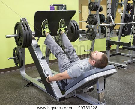Man Using Plate Loaded Leg Press.  Focus on foot area.