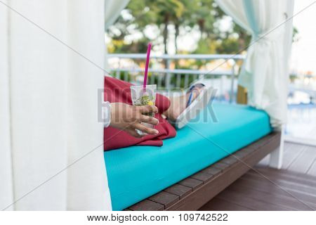 Woman sitting on resort pool and drinking juice
