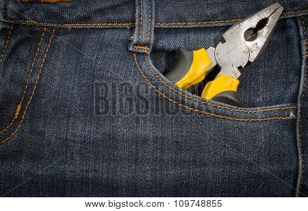 Pliers With Yellow Handle In A Pocket Of Jeans.  Background.