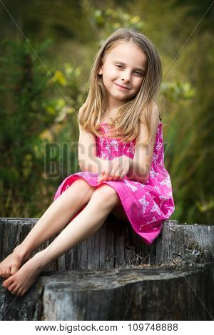 Portrait of little girl sitting on tree stump