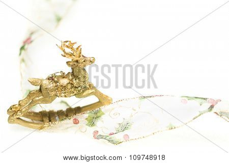 Decorative Christmas Reindeer Ornament and Ribbon on White Background.