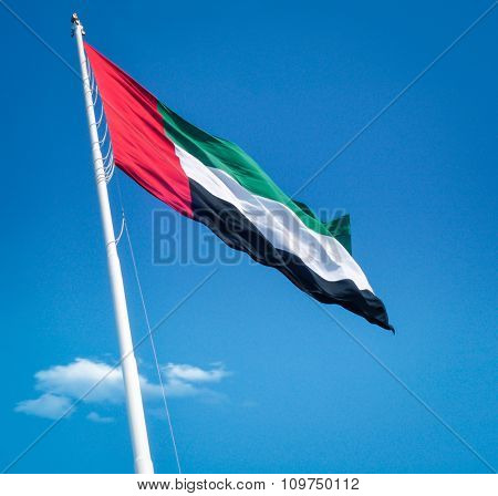 National flag of UAE flying against clean blue sky and subtle clouds. Below angle view.