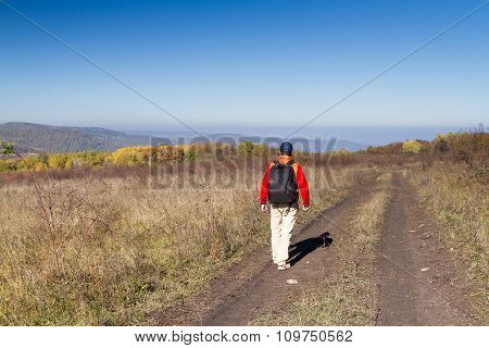 Male Tourist With Backpack Is On A Rural Road