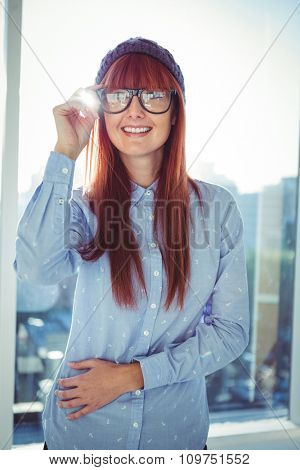 Portrait of smiling hipster woman posing in a bright room