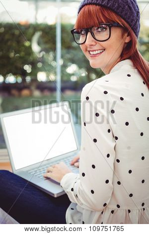 Attractive hipster woman using laptop in a bright room