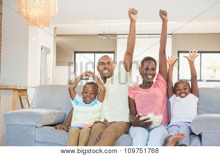 Happy family watching television eating popcorn in living room