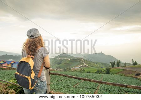 Young Woman With Backpack Looking To Mountain View
