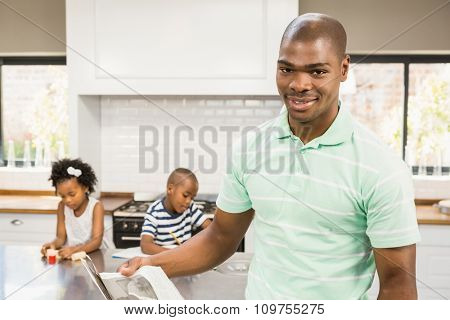 Smiling father reading newspaper in the kitchen