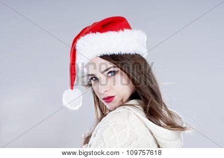 Christmas Woman. Beautiful Charming Girl Wearing  Santa Hat Over Blue Background.