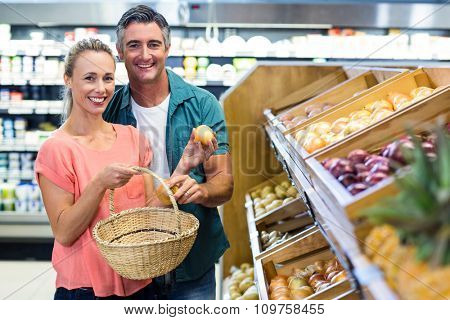 Happy couple at the supermarket holding potatoes