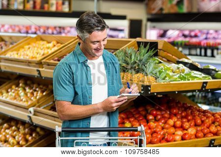 Smiling man looking at his list at the supermarket