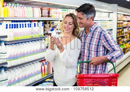 Smiling couple buying milk at the supermarket