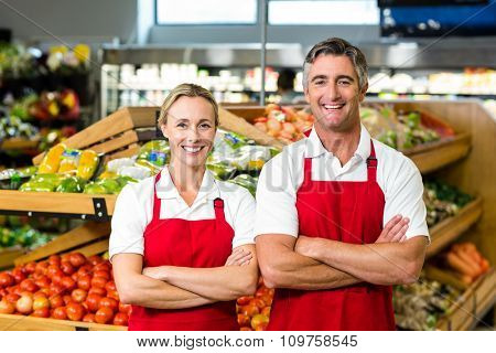 Portrait of smiling couple wearing apron in supermarket