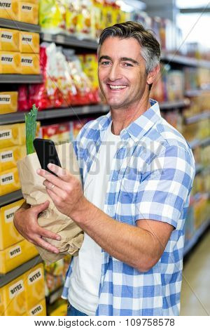 Smiling man with grocery bag using smartphone at the supermarket