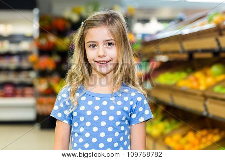 Smiling young girl looking at camera at supermarket