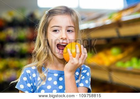 Smiling young girl eating an orange at supermarket
