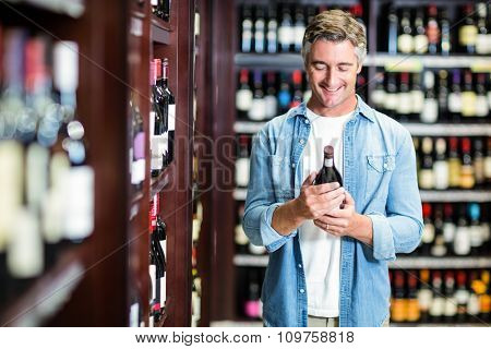 Smiling man holding bottle of wine in supermarket