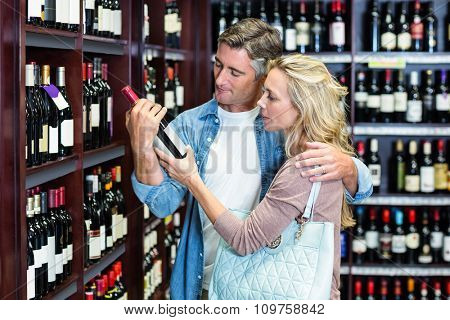 Smiling casual couple looking at wine bottle in supermarket