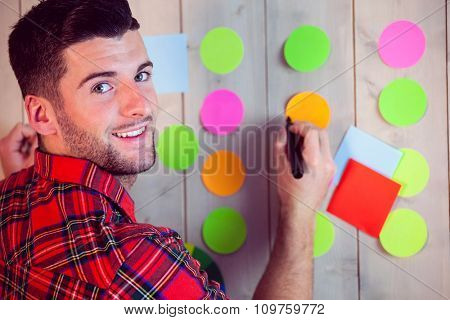Creative worker using wall for brainstorm in his office