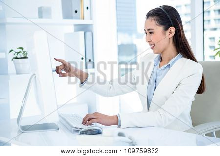 Smiling businesswoman pointing her screen at the desk in work
