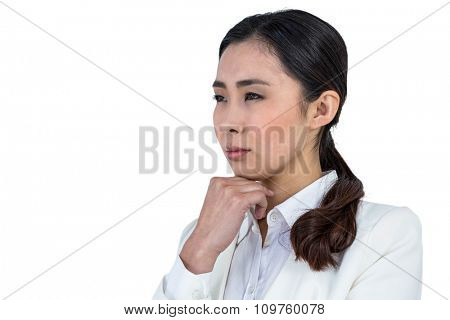 Focused businesswoman with hand on chin against white background