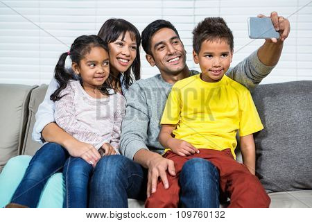 Happy family taking selfie on the sofa in living room