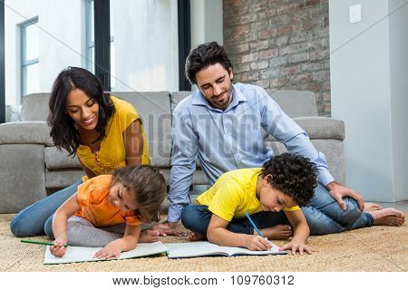 Family sitting on carpet in living room with children drawing