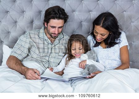 Happy family on bed reading book at home