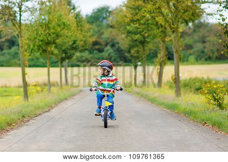 Adorable kid boy of 4 years riding on bicycle