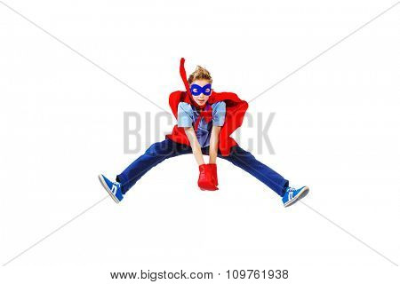 A boy teenager in a costume of superhero is jumping. Isolated over white background.