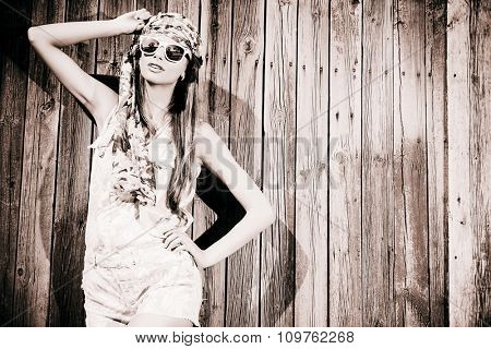 Beautiful romantic young woman in casual summer clothes stands by the old wooden fence. Outdoor fashion. Jeans style. Toned photo, sepia.