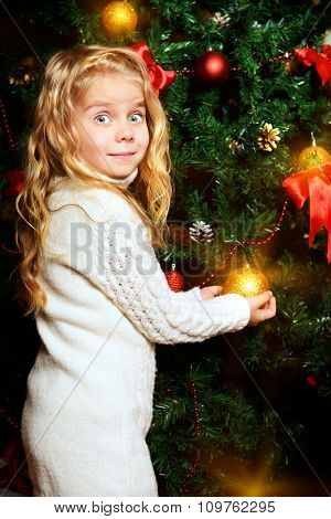 Angelic little girl decorating Christmas tree with balls.