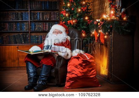 Santa Claus sitting at his home in a comfortable chair and reading a letter.