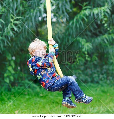 Little smiling boy of three years having fun on swing