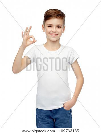 childhood, fashion, advertisement and people concept - happy boy in white t-shirt and jeans showing ok hand sign