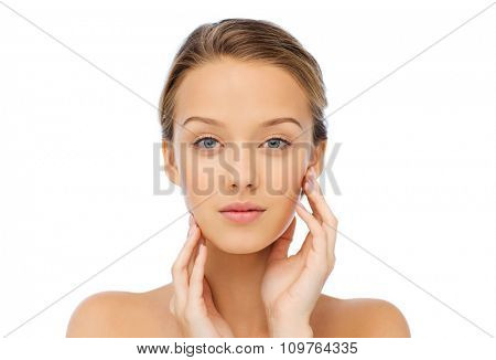 beauty, people and health concept - young woman with bare shoulders touching her face