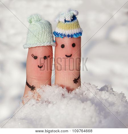 Finger art of a Happy couple on the background of snow. A man and a woman hug.
